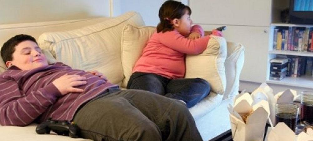 bambino obesi che stanno sul divano a guardare la televisione
