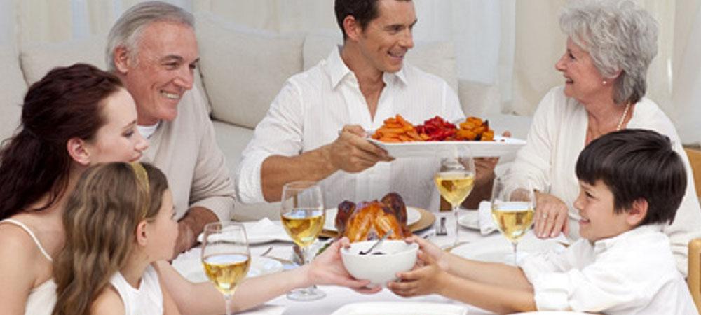 famiglia a tavola sorridente con nonni figli e nipoti